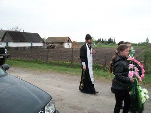 The priest leading the way to the cemetery